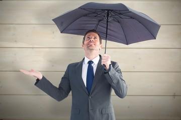 Composite image of businessman sheltering under black umbrella