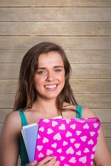 Composite image of smiling young woman with books