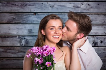 Composite image of man kissing woman as she holds flowers