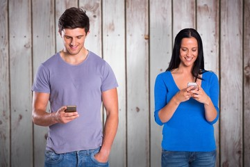 Composite image of young couple sending a text