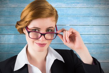 Composite image of redhead businesswoman touching her glasses