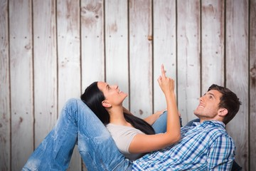 Composite image of young couple lying on floor smiling