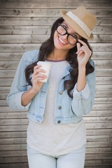 Composite image of brunette with disposable cup