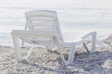 White plastic loungers to relax on beach