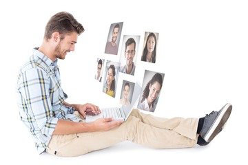 Composite image of handsome young man sitting using laptop