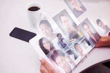 Composite image of smiling designer using tablet