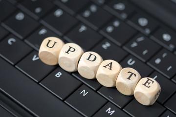 Tastatur und Holzwürfel mit dem Wort Update