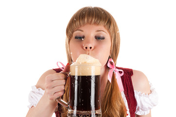Oktoberfest waitress blows with beer foam isolated on white