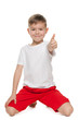 Little boy holds his thumb up