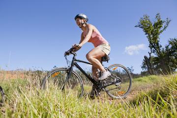 Woman mountain biking on country track