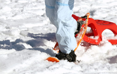 woman walking with snowshoes on freshly-fallen snow