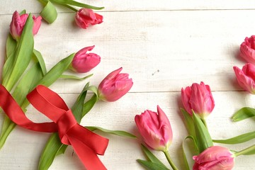Pink tulips with red ribbon on white wooden background