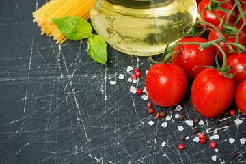 dark background with cherry tomatoes, pasta, fresh basil
