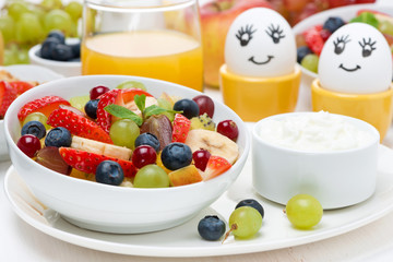 fresh fruit salad, cream and painted eggs for breakfast, closeup