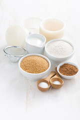 Ingredients for baking muffins on white table, vertical