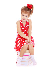 Adorable little girl in red dress sitting on a pile of books.