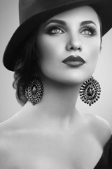 beautiful girl with makeup in hat and earrings, black and white
