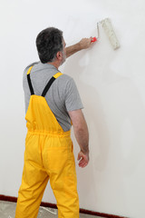 Worker painting white wall in a room with paint roller
