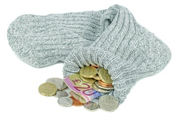 An old woolen sock full of British money on a white background