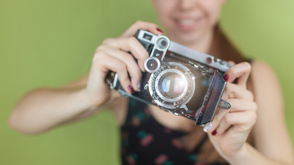 smiling girl with vintage  retro camera taking photo on green