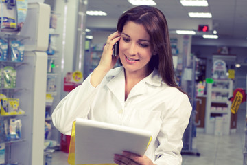 Happy female pharmacist on the phone in pharmacy