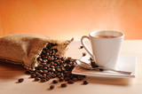 Cup of coffee and sack with coffee beans and orange background