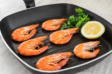 cooked shrimps with lemon and parsley in a pan