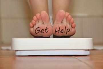 Feet on bathroom scale with hand drawn Get Help text