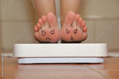 Feet on bathroom scale with hand drawn sad cute faces - 78438295