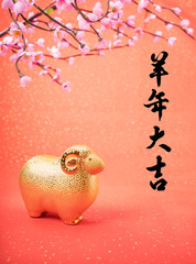Ceramic goat souvenir on red paper,2015 is year of the goat