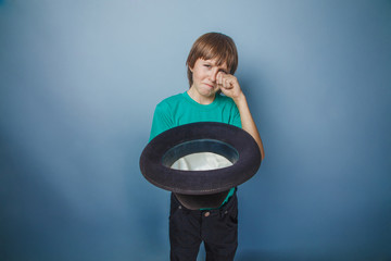 European-looking boy of ten years beggar, poor, asks for money o