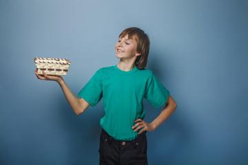 European-looking boy of ten years holding an empty basket in han