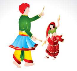 Traditional indian copule playing dandiya