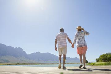 Senior couple walking on wooden jetty