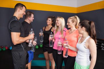 Fitness Group having a bottle of water and talking to each other