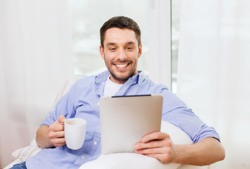 smiling man with tablet pc and cup at home