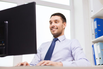 smiling businessman with computer in office