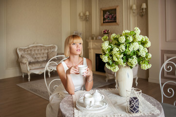 Young blond woman drinking tea at home