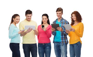 group of teenagers with smartphones and tablet pc