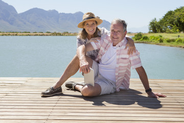 Senior couple sitting on wooden jetty with digital tablet