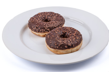 Two ring donuts with chololate glaze on white plate
