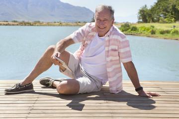 Senior man sitting on jetty with digital tablet
