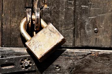 Old wooden door locked with padlock.