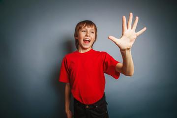 European-looking boy of ten years shows a figure five fingers on