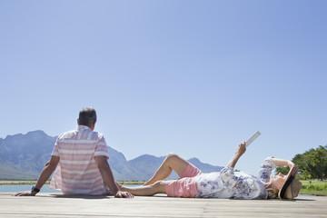 Senior couple sitting on wooden jetty reading digital tablet