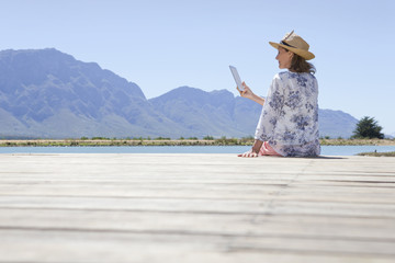 Senior woman sitting on jetty with digital tablet