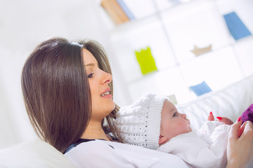 Young woman holding her baby in her arms