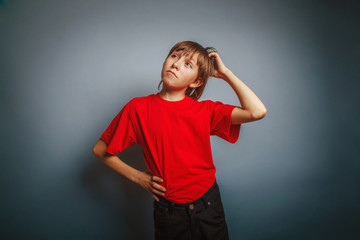European-looking boy of ten years thinking, scratching his head