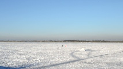 Man and woman walking on ice of frozen water storage reservoir
