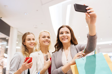 women with smartphones shopping and taking selfie
